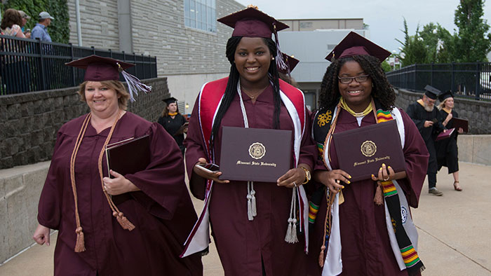 Three Missouri State graduates walking in their cap and gowns with their diplomas.